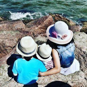 Three children sitting on rocks overlooking sea green sea water.