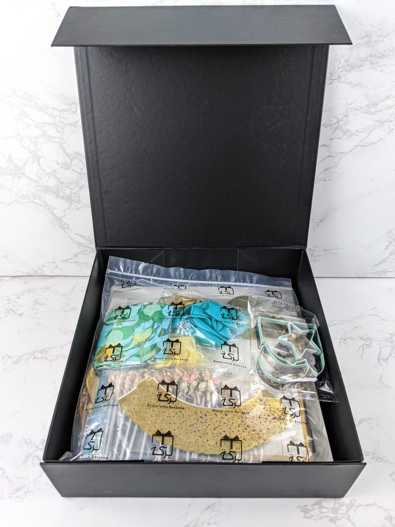 Opened Square black Eid Barakah box with contents in a plastic bag
